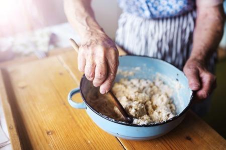 Photo pour Senior woman baking pies in her home kitchen.  Mixing ingredients. - image libre de droit
