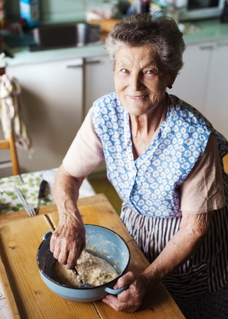 Foto per Senior woman baking pies in her home kitchen.  Kneading dough. - Immagine Royalty Free