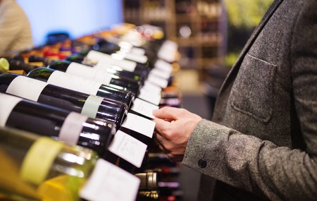 Photo pour Unrecognizable young man in a wine shop choosing a wine - image libre de droit