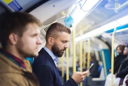 Photo pour Young handsome businessman with smartphone in subway - image libre de droit