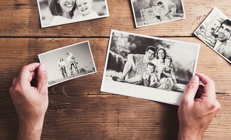 Photo for Black and white family photos laid on a table. Studio shot on wooden background. - Royalty Free Image