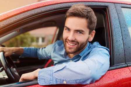 Photo for Handsome young man in a blue shirt driving a car - Royalty Free Image