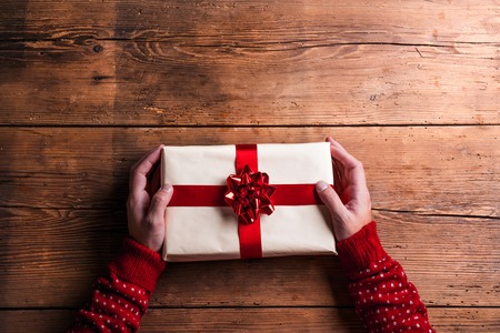 Photo for Man holding Christmas present laid on a wooden table background - Royalty Free Image