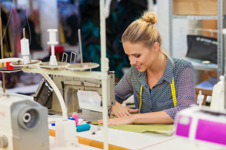 Foto per Beautiful young woman sewing clothes with sewing machine. - Immagine Royalty Free