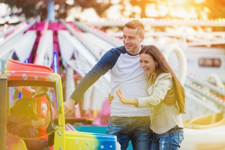 Photo for Beautiful young family enjoying their time at fun fair - Royalty Free Image