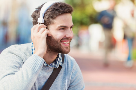 Photo for Handsome young man with white headphones outside in the town - Royalty Free Image