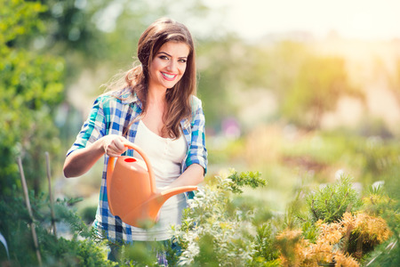 Photo for Beautiful young woman gardening outside in summer nature - Royalty Free Image