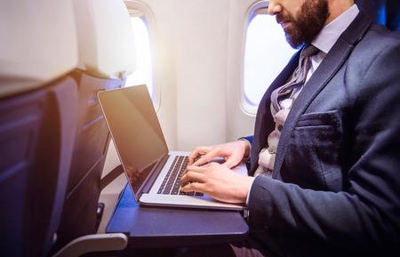 Photo pour Unrecognizable young businessman with notebook sitting inside an airplane - image libre de droit