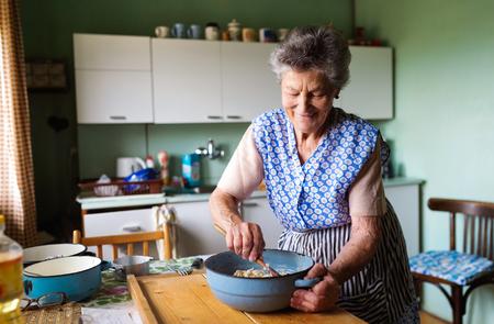 Foto de Senior woman baking pies in her home kitchen.  Mixing ingredients. - Imagen libre de derechos