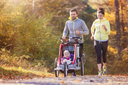 Foto de Beautiful young family with baby in jogging stroller running outside in autumn nature - Imagen libre de derechos
