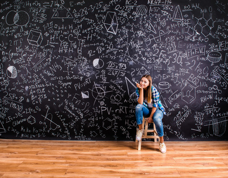 Photo for Beautiful young school girl in front of big blackboard - Royalty Free Image