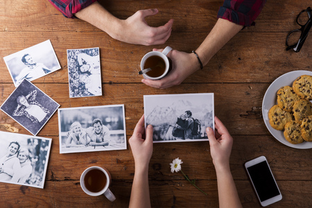 Photo pour Unrecognizable mans and womans hand. Looking  at their black and white photos. Couple in love. Cookies and tea, daisy flower, smart phone. Valentines day composition. Studio shot on brown wooden background. - image libre de droit