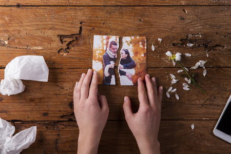 Photo pour Unrecognizable woman holding torn picture of couple in love. Ended relationship. Crying.Valentines day composition. Studio shot on brown wooden background. - image libre de droit