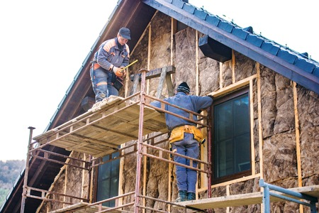 Photo pour Construction workers standing on scaffold thermally insulating house facade with glass wool. - image libre de droit