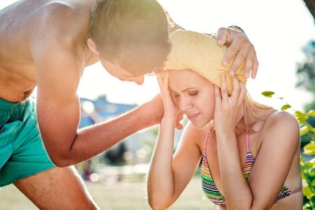 Foto de Young man helping woman in bikini with heatstroke, summer heat, sunny day - Imagen libre de derechos