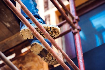 Photo pour Close up of legs and soles of unrecognizable man standing on scaffold - image libre de droit
