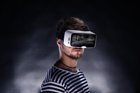 Foto de Hipster man in striped black and white sweatshirt wearing virtual reality goggles. Studio shot on black background - Imagen libre de derechos