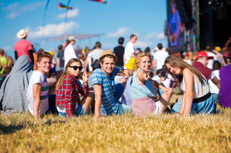 Foto de Group of teenagers at summer music festival, sitting on the grass in front of stage, back view, rear, viewpoint - Imagen libre de derechos