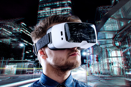 Photo pour Man wearing virtual reality goggles against illuminated night city - image libre de droit