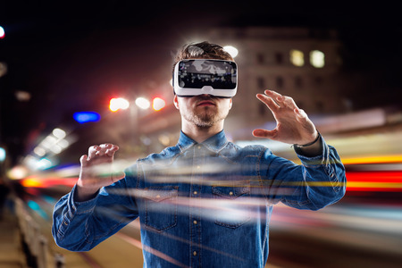 Foto de Double exposure of man wearing virtual reality goggles and night city - Imagen libre de derechos
