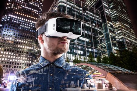 Foto de Double exposure of man wearing virtual reality goggles and night city - Imagen libre de derechos