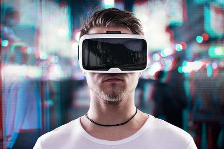 Foto de Man wearing virtual reality goggles against illuminated night city - Imagen libre de derechos
