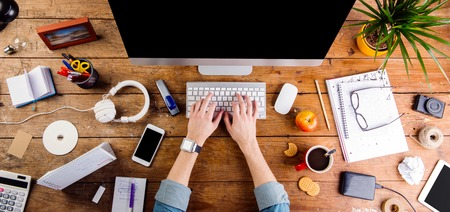 Foto de Business person working at office desk. Smart watch on hand and smart phone on the table. Coffee cup, notepad and glasses and various office supplies around the workplace. Flat lay. - Imagen libre de derechos