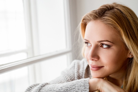 Photo for Beautiful blond woman sitting on window sill, looking out of window - Royalty Free Image