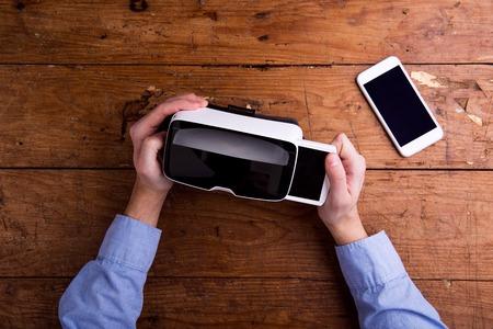 Foto de Hands of man holding virtual reality goggles and smart phone. Flat lay. Studio shot on wooden background. - Imagen libre de derechos