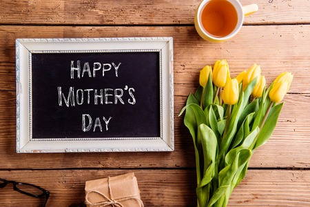Photo for Mothers day composition. Picture frame with chalk sign, bouquet of yellow tulips, gift and cup of tea. Studio shot on wooden background. - Royalty Free Image