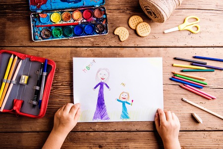Photo for Mothers day composition. Hands of unrecognizable child drawing picture of her and her mother. Studio shot on wooden background. - Royalty Free Image