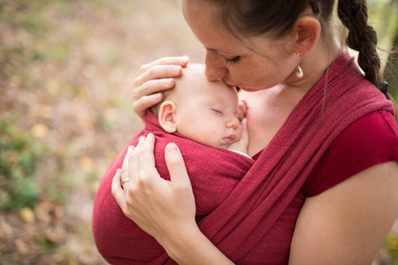 Photo for Mother carrying her cute baby daughter in sling, kissing her, outside in autumn nature - Royalty Free Image