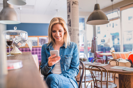 Photo pour Blond woman in denim shirt sitting at the bar in modern city cafe, holding a smart phone, texting - image libre de droit
