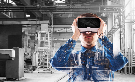 Photo pour Hipster man in denim shirt wearing virtual reality goggles. Welding factory. - image libre de droit