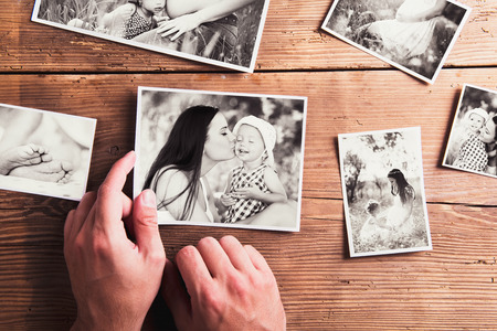 Photo for Mothers day composition. Hands of unrecognizable man holding  black-and-white photo. Studio shot on wooden background. - Royalty Free Image