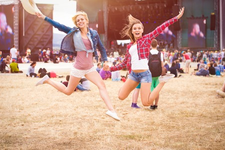 Foto de Teenage girls at summer music festival, in front of stage, jumping - Imagen libre de derechos