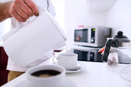 Photo pour Unrecognizable man preparing coffee. Pouring hot water from electric kettle into prepared cups. - image libre de droit