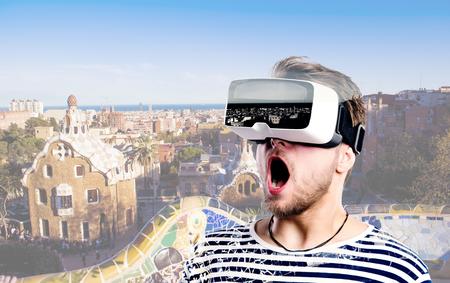 Foto de Hipster man in striped black and white sweatshirt wearing virtual reality goggles. Park Guell, Barcelona, Spain. - Imagen libre de derechos