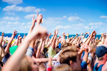 Foto de Teenagers at summer music festival under the stage in a crowd enjoying themselves, clapping and singing - Imagen libre de derechos