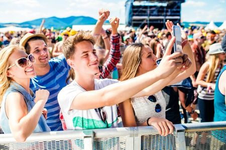 Foto de Teenagers at summer music festival in crowd taking selfie with smartphone, enjoying themselves - Imagen libre de derechos