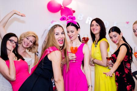 Photo pour Cheerful bride and happy bridesmaids celebrating hen party with drinks. Women enjoying a bachelorette party dancing. - image libre de droit