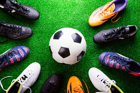 Soccer ball and cleats against artificial turf, studio shot on green background.