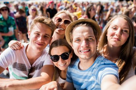 Foto de Teenagers at summer music festival in crowd taking selfie, enjoying themselves - Imagen libre de derechos