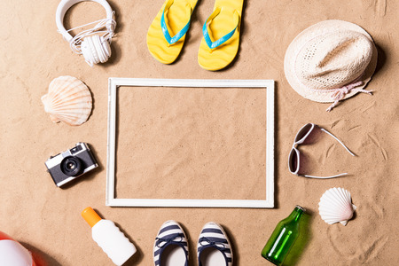 Foto de Summer vacation composition with picture frame, pair of yellow flip flop sandals, hat, sunglasses, sun cream and other stuff on a beach. Sand background, studio shot, flat lay. Copy space. - Imagen libre de derechos