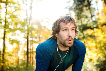 Foto de Young handsome runner with earphones in his ears, listening music, outside in sunny autumn nature, resting, breathing out - Imagen libre de derechos