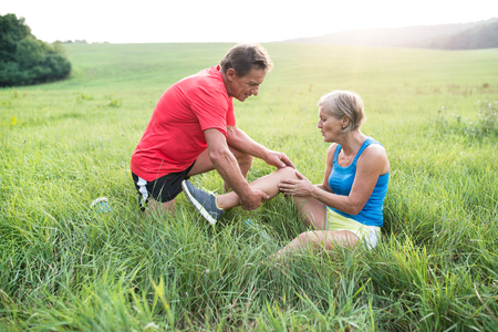 Foto de Active senior runners outside in field. Woman with injured knee. Man helping her. Green sunny summer nature. - Imagen libre de derechos