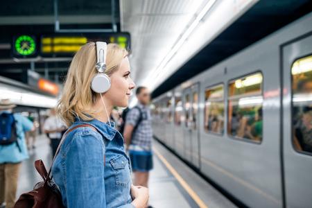 Foto de Beautiful young blond woman in denim shirt with earphones, standing at the underground platform, waiting to enter a train - Imagen libre de derechos