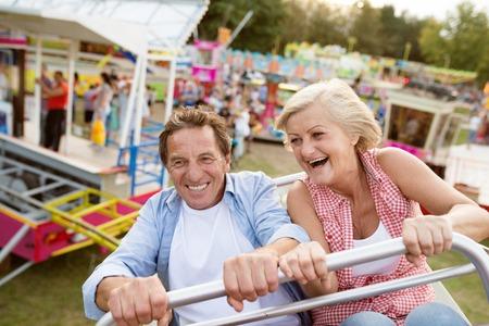 Foto de Senior couple having fun on a ride in amusement park. Summer vacation. - Imagen libre de derechos
