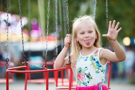 Photo for Cute little girl enjoing time at fun fair, chain swing ride, amusement park in summer - Royalty Free Image