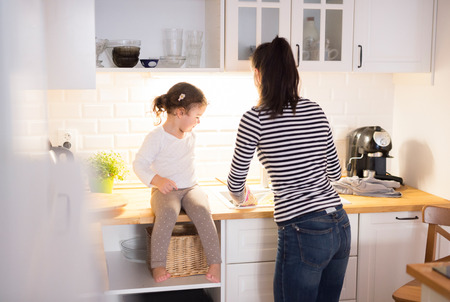 Photo pour Beautiful young mother with her cute little daughter in the kitchen, cooking pasta together - image libre de droit